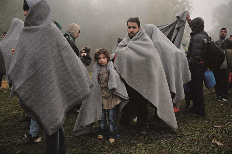 Refugees and migrants in the meadow, the green border, Rigonce, 25 Oct  2015, refugees Slovenia © Borut Krajnc
